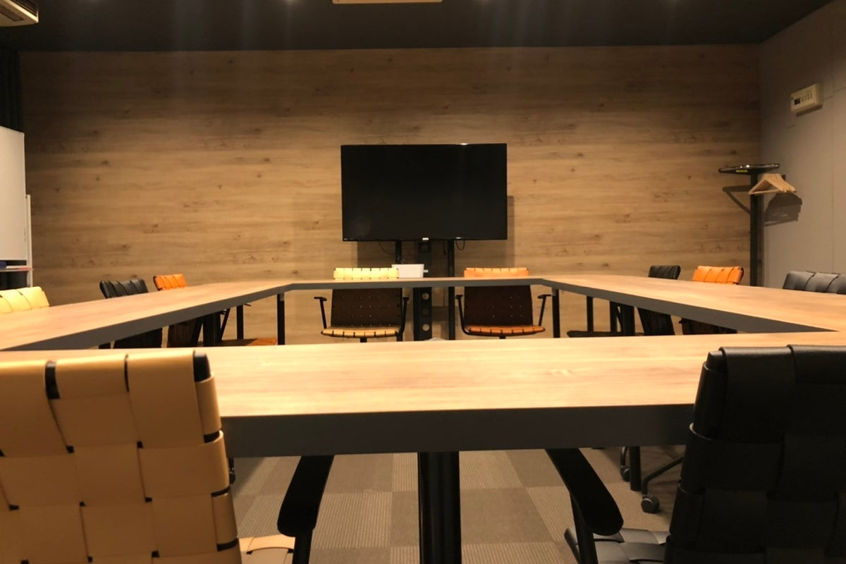 広瀬通【仙台協立第1ビル2階2-D貸会議室】12名様用 木目調の円卓とオシャレなレザーチェアがモダンな会議室 の写真