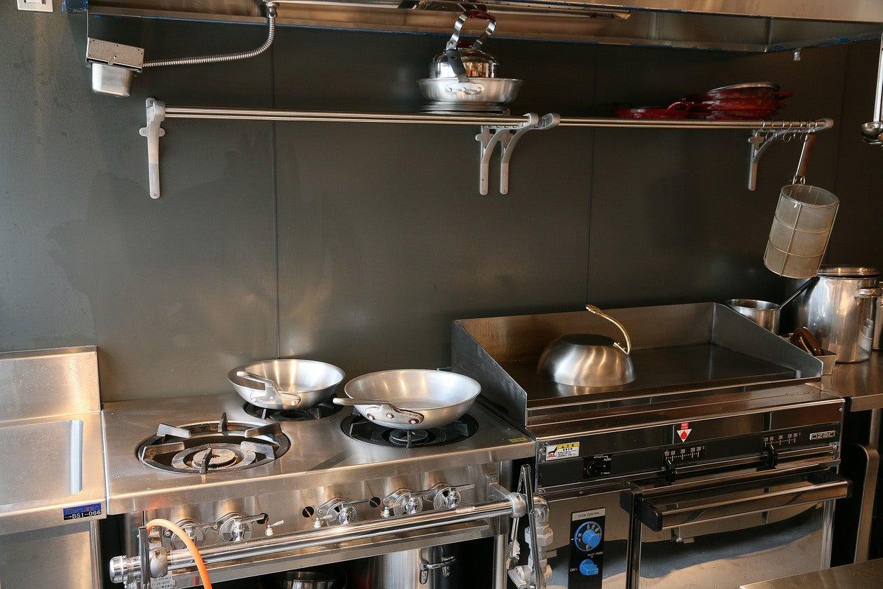 キッチン 左から1槽シンク、三口ガスコンロ、上鉄板、下ガスオーブン
